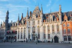 Brugge - Grote Markt en het gotische gebouw van Provinciaal Hof en Historium-de bouw in avond Royalty-vrije Stock Foto's