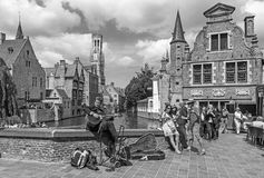 Brugge - View from the Rozenhoedkaai in Brugge with the street musician and the Perez de Malvenda house and Belfort van Brugge Stock Photos