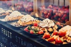 Brugge, West-Vlaanderen, België, 19 Oktober, 2018: Belgische wafels met aardbei, braambes en room in het winkelvenster stock afbeelding