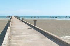 Brugsteen op het strand en overzees met blauwe hemel Stock Fotografie