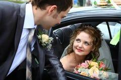 Bruid in auto en bruidegom Stock Afbeeldingen