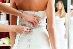 Bruid bij de klerenwinkel voor huwelijkskleding stock fotografie