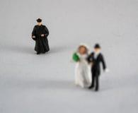 Bruid, bruidegom en priester op wit Royalty-vrije Stock Foto's