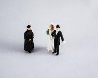 Bruid, bruidegom en priester op wit Stock Foto's