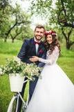 Bruid & bruidegom het stellen dichtbij fiets Stock Foto's