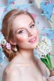 Bruid De jonge mannequin met perfecte huid en maakt omhoog, bloemen in haar Mooie vrouw met make-up en kapsel in slaapkamer Stock Foto's