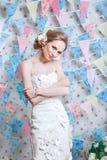 Bruid De jonge mannequin met perfecte huid en maakt omhoog, bloemen in haar Mooie vrouw met make-up en kapsel in slaapkamer Royalty-vrije Stock Afbeeldingen