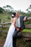 Bruid die de Bruidegom omhelst tegen een omheining Stock Foto's