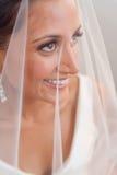 Bruid die door haar sluier en het glimlachen kijkt Stock Foto