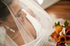 Bruid die door haar sluier haar boeket bekijkt Royalty-vrije Stock Foto