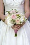 Bruid die een boeket van huwelijksbloemen houdt Stock Foto's