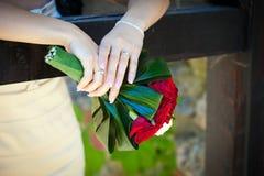 Bruid die een huwelijksboeket houdt Stock Foto