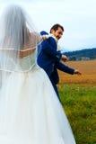 Bruid die haar bruidegom aan haar met een kabel trekken - grappig huwelijksconcept stock afbeeldingen