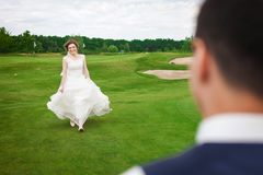 Bruid die haar bruidegom op een groene weide lopen te ontmoeten Royalty-vrije Stock Fotografie