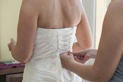 Bruid die haar geëlimineerde kleding hebben Stock Foto