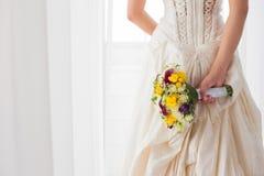Bruid die haar huwelijksbloemen achter haar tegenhouden Royalty-vrije Stock Afbeelding