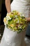 Bruid die haar huwelijksboeket houdt Stock Afbeelding