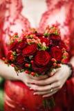 Bruid die haar rood huwelijksboeket van bloemen houden Royalty-vrije Stock Foto