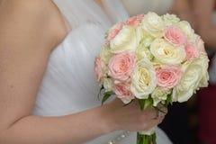 Bruid die haar rozenboeket houden Stock Fotografie