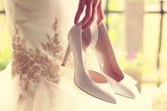 Bruid die haar schoenen houden Royalty-vrije Stock Afbeeldingen