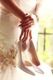 Bruid die haar schoenen houden Stock Afbeeldingen