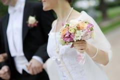 Bruid die het mooie boeket van huwelijksbloemen houdt Stock Foto