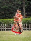 Bruid die in kimono van honkbal in het festival van Kersenbloesems in park genieten Royalty-vrije Stock Fotografie