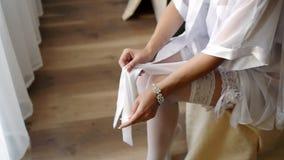 Bruid die kousen uittrekken die klaar voor haar huwelijk in haar slaapkamer worden - de partij schoot 2 stock videobeelden