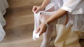 Bruid die kousen uittrekken die klaar voor haar huwelijk in haar slaapkamer - zijschot worden stock videobeelden