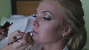 Bruid die make-up doen vóór het huwelijk Een jonge vrouw neemt een stilist stock footage