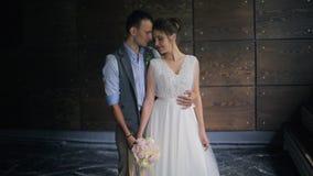 Bruid die met boeket en bruidegomtribune in greep elkaar bekijken stock video