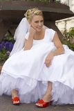 Bruid die met Rode Schoenen op Rand zit royalty-vrije stock foto's