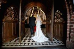 Bruid die onderaan doorgang met vader lopen stock foto
