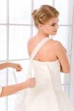 Bruid die op haar witte huwelijkskleding zetten Royalty-vrije Stock Afbeeldingen