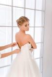 Bruid die op haar witte huwelijkskleding zetten Stock Foto's