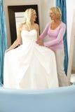 Bruid die op huwelijkskleding probeert met verkoopmedewerker Stock Afbeelding