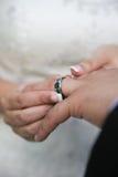Bruid die op trouwring zet Royalty-vrije Stock Foto's