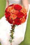 Bruid die oranje boeket houdt Stock Foto's