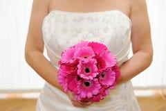Bruid die roze bloemen houdt royalty-vrije stock foto's