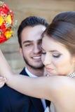 Bruid die terwijl het omhelzen van de bruidegom glimlachen Stock Afbeelding