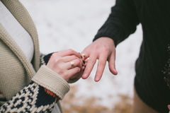 Bruid die trouwring op bruidegomsvinger zetten Stock Foto