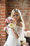 Bruid die in witte kleding met krullend haar het boeket snuiven Royalty-vrije Stock Foto