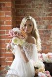 Bruid die in witte kleding met krullend haar het boeket snuiven Stock Foto's