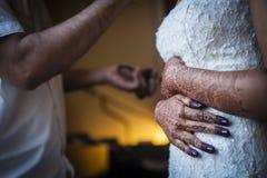 Bruid die zich omhoog kleedt Stock Foto