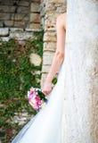 Bruid die zich terug naar de witte kolom met boeket in de hand bevinden Stock Afbeeldingen