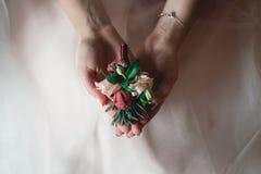 Bruid in een luxueuze huwelijkskleding die een huwelijksknoopsgat houden die van rozen wordt gemaakt stock foto's