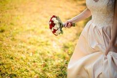 Bruid in een witte huwelijkskleding die met een beauriful rood rozenboeket lopen royalty-vrije stock fotografie