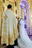 Bruid en bruidegom bij de kerk tijdens een huwelijksceremonie royalty-vrije stock afbeeldingen