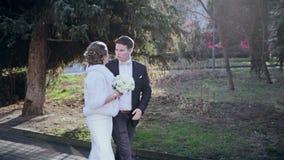 Bruid en bruidegom bij een park op hun huwelijksdag stock footage
