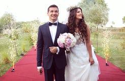 Bruid en bruidegom bij het rode tapijt omringen door firew Stock Afbeeldingen